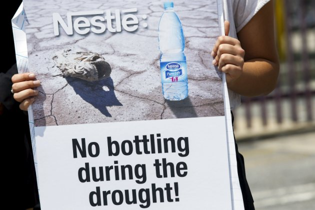 A demonstrator holds a sign during a march to protest against Nestle bottling water during the California drought, outside a Nestle Arrowhead water bottling plant in Los Angeles, May 20, 2015. Despite the current California drought, the total volume of bottled water consumed in the United States hit 11 billion gallons last year, up more than 7 percent from 2013. That translated into an average of 34 gallons per person, according to the International Bottled Water Association, citing data from the Beverage Marketing Corp. REUTERS/Patrick T. Fallon