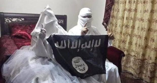 Eine ISIS militanten mit seiner Braut winkenden Flagge der Gruppe in einem Schlafzimmer. Datei-Foto