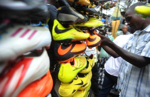 SIMON MAINA VIA GETTY IMAGES Ein Kunde prüft Fußballschuhe im Gikomba-Markt, dem größten Markt für Second-Hand-Kleidung Ostafrikas, am 10. Juli 2014, in Nairobi, Kenia