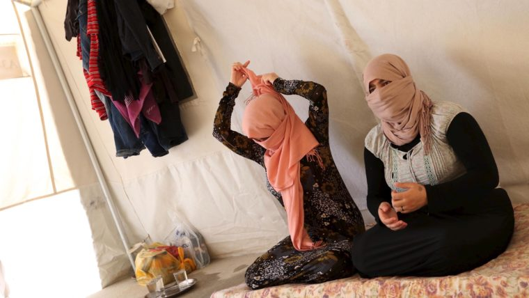 Yazidi sisters, who escaped from captivity by Islamic State (IS) militants, sit in a tent at Sharya refugee camp on the outskirts of Duhok province July 3, 2015. The sisters were among one hundred women, men and children taken by IS as prisoners after the militants attacked their village of Tal Ezayr in the northern Iraqi province of Mosul close to Syrian border last year. In an interview with Reuters TV, the sisters talked about their horrific ordeal, treatment of women by the militants, and their eventual escape. Picture taken July 3, 2015. REUTERS/Ari Jala - RTX1LE9W